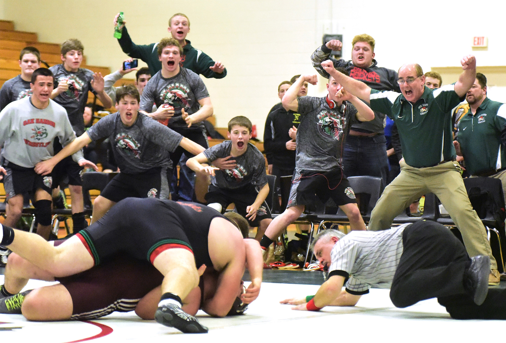 Oak Harbor's wrestling team reacts to Zach Laughlin wrestling Genoa's Christian Aranda in the match that put Oak Harbor ahead 29-26, the team's first lead of the night.