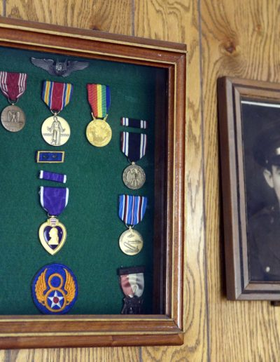 Charles Holcomb displays his metals in his home next to a photograph of himself during his service in WWII.