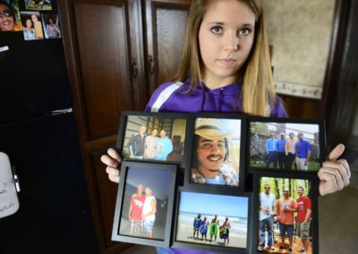 Bralyn Gregg, 15, of Clyde holds family photos featuring her brother, Bryce Williamson, who died of a drug overdose.