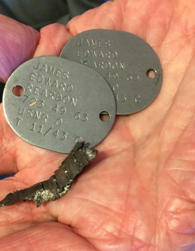 James Reardon holds his dog tags from WWII with a piece of shrapnel he found on the deck of his ship.