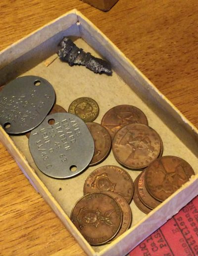 James Reardon keeps his dog tags from WWII, a piece of shrapnel he found on the deck of his ship, and money from WWII in a box.