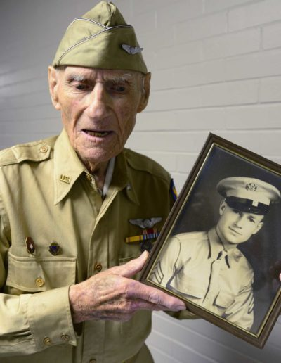 Jim McGrady holds a picture of himself from 1942 when he served in field artillery during WWII.