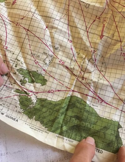 """Leo Bundschuh hold a silk map of New Guinea he kept inside his uniform in case he was shot down or crashed. """"Hopefully you would know where you were,"""" he joked. """"That's the trouble with the Pacific being so big."""""""