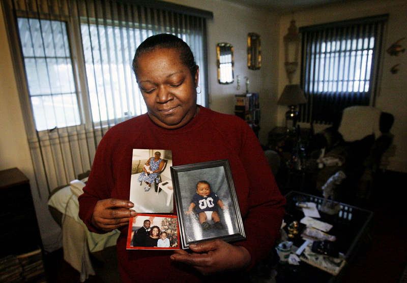 Gloria Edmond holds photos of three of her relatives murdered in a house fire on St. John Ave. in Toledo, including her sister, Rose Mary McCollum, whose ex-boyfriend Wayne Powell was given the death penalty for the setting the fire.