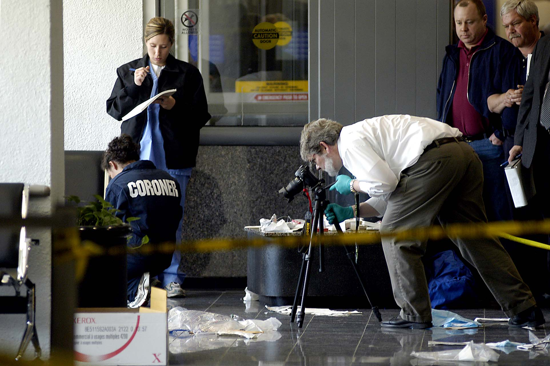 An investigator photographs evidence at Cleveland Hopkins International Airport where a police officer shot and killed Kenneth Calloway, 38, of Cleveland. Calloway argued with a Delta employee after trying unsuccessfully to buy a ticket. He went to the adjacent United Airlines counter and bought a ticket to Chicago, where employees notified the police. In a confrontation, Calloway grabbed an officer's gun and shot a patrolman Steve Walker, 52, before he was killed by a third officer.