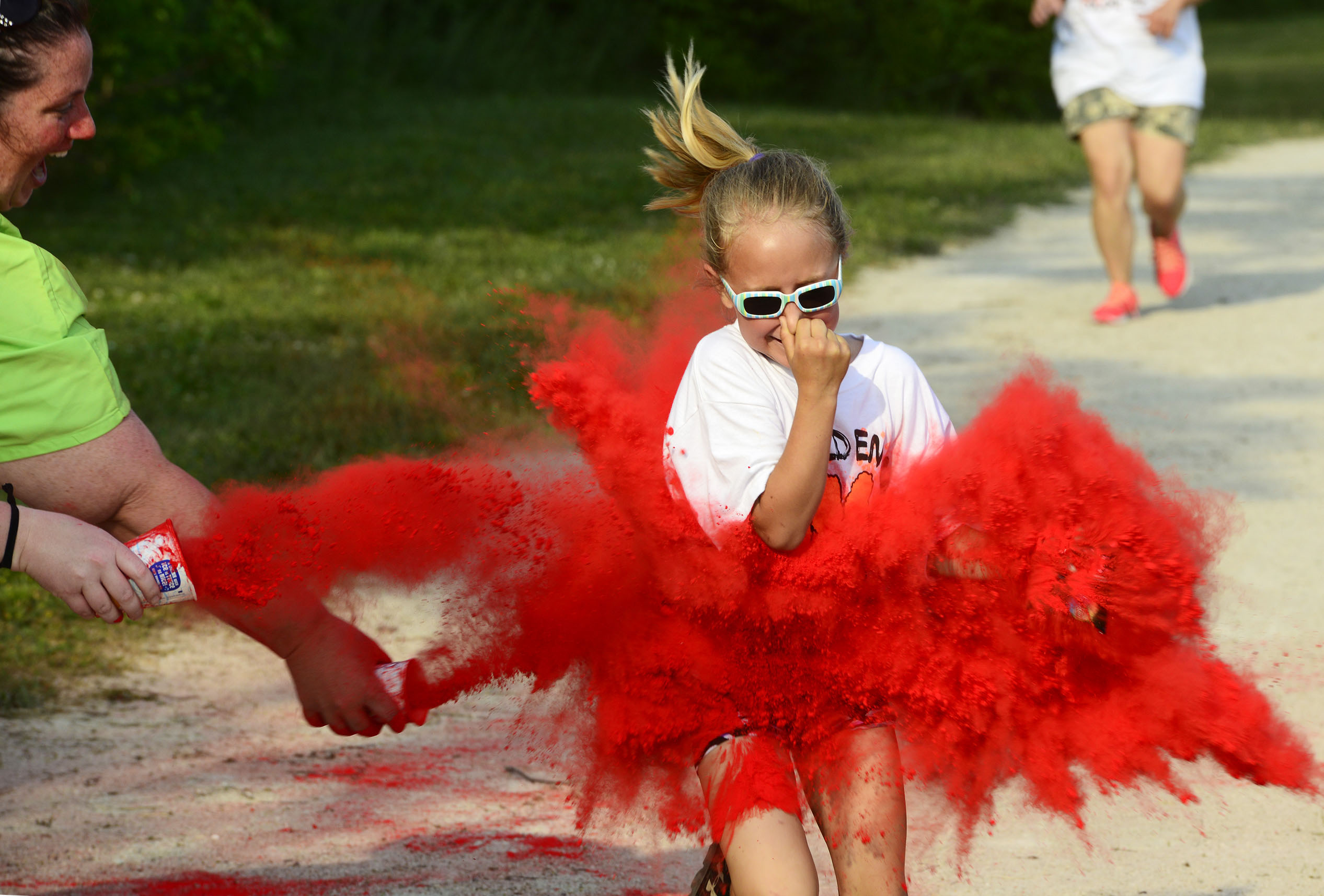 Ashlyn Wightman, 7, of Gibsonburg runs in the Golden Bear Color Run on Friday evening, competing in her first run.