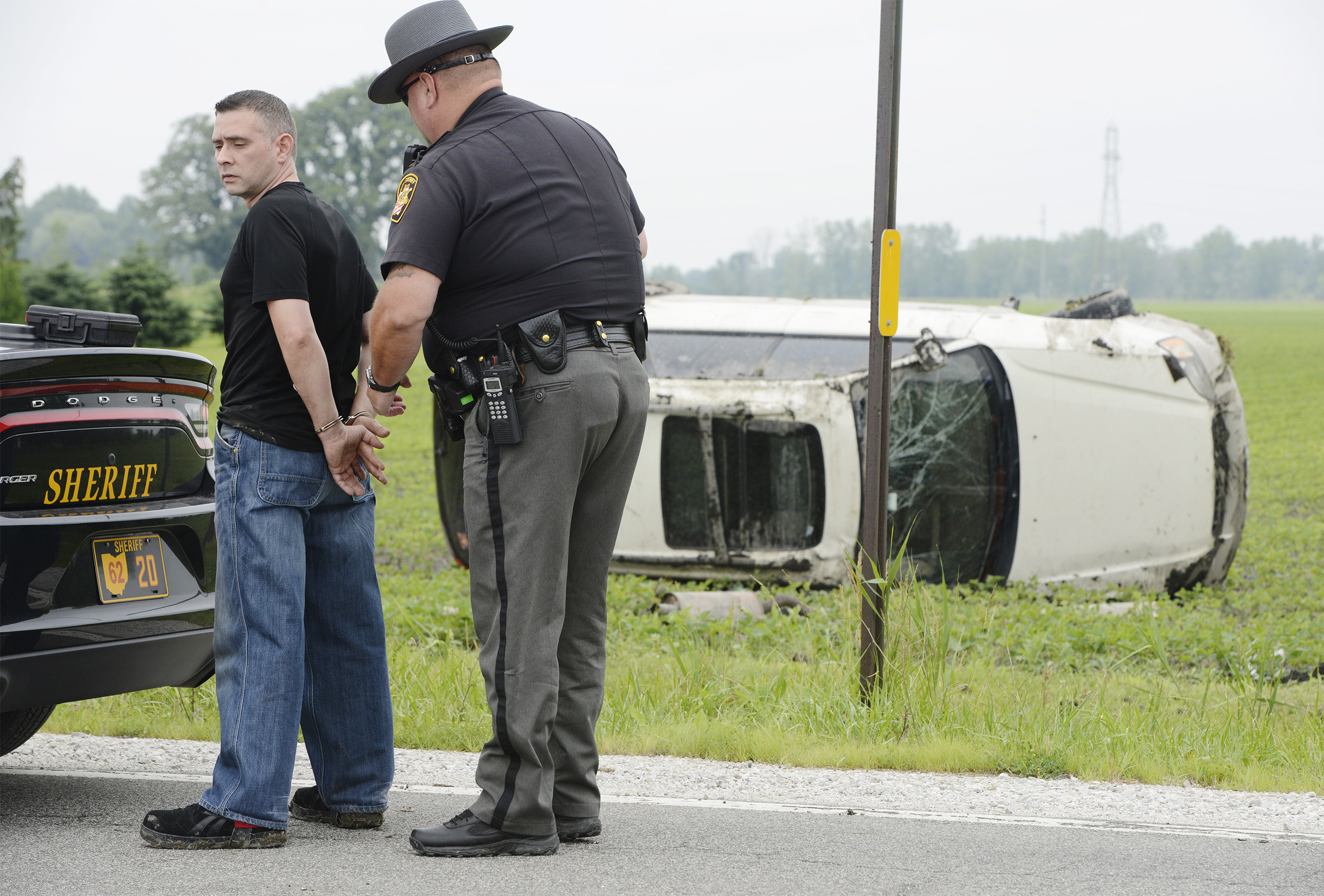 Sgt. Kent Davis, of the Ottawa County Sheriff's Office, arrests William Mitchell after a single-vehicle crash. Mitchell reportedly turned onto County Road 17 from Ohio 53, drove off the road and rolled his car several times in a field.