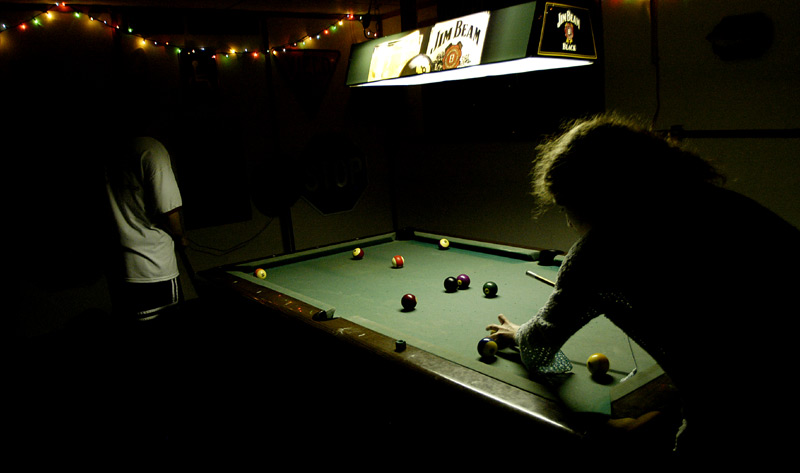 Evan, left, and Piper shoot pool in the basement of the Zeta Chi fraternity house.