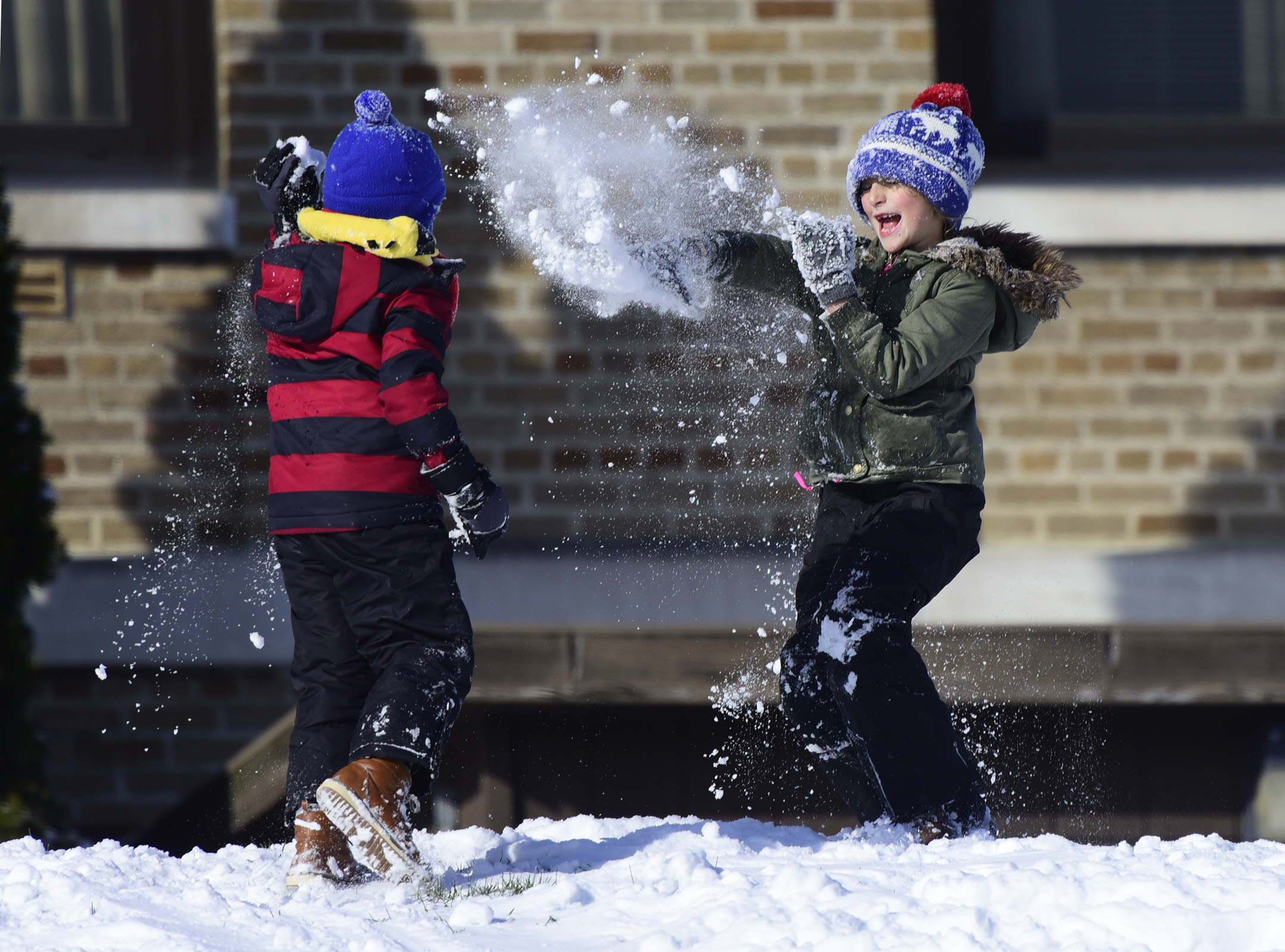 Mia Conrad, 7, of Gibsonburg, right, throws a snow ball at her brother, Zander, 5.
