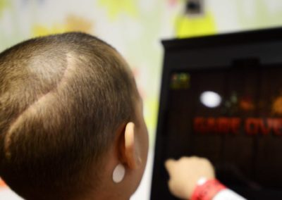 After a nap and eating snacks, Tae plays video games in the playroom at UH Rainbow while chemotherapy drugs are pumped into him.