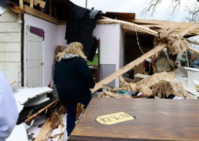 """Connie Weyer, right, walks through her home destroyed by a tornado. Every Sunday, the Weyer family eats dinner together. But, on Nov. 5, the family went bowling. """"If we were here, my grandkids would have been playing in this room when the tornado hit,"""" Connie said."""