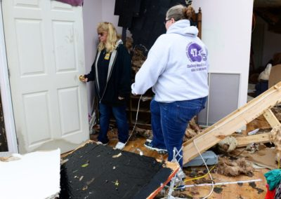 """Connie Weyer, left, walks through her home destroyed by a tornado. Every Sunday, the Weyer family eats dinner together. But, on Nov. 5, the family went bowling. """"If we were here, my grandkids would have been playing in this room when the tornado hit,"""" Connie said."""