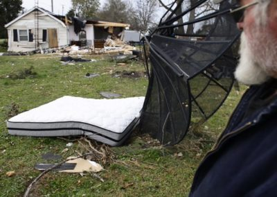Kevin Weyer looks at his mother-in-law's mattress blown halfway across the yard by an EF 1 tornado. His mother-in-law was in the living room when the tornado hit. She described the tornado as sounding like a whistle which only lasted a few seconds. The force of the wind blew her bedroom door shut. The door then blew open, and when she looked out the bedroom was gone.
