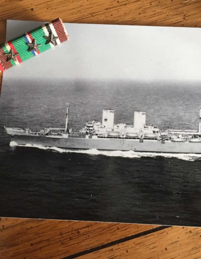 The USS General W. H. Gordon, the troop transport ship that took Walter Auxter to Cherbourg, France, next to his ribbon bars with stars from WWII.