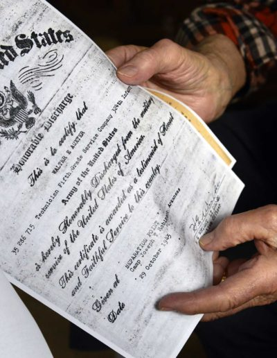 Walter Auxter holds a copy of his honorable discharge certificate.